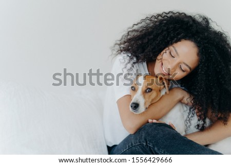 Photo of attractive woman with curly Afro hairstyle, cuddles and pets dog with smile, expresses love Stock photo © vkstudio