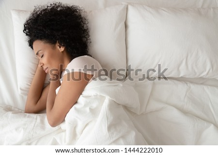 Young pretty African American woman rests in bed at home, drinks hot tea in morning, enjoys domestic Stock photo © vkstudio
