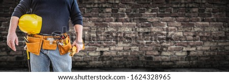 Contractor With Tool Belt and Hard Hat In Front of Aged Brick Wa Stock photo © feverpitch