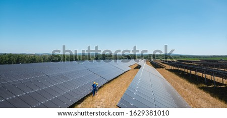 Large photovoltaic power plant with people standing at the panels Stock photo © Kzenon