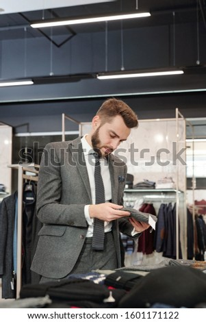 Young well-dressed man looking through new collection in boutique Stock photo © pressmaster