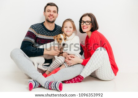 Isolated shot of good looking female and male sit together with their daughter and jack russell terr Stock photo © vkstudio