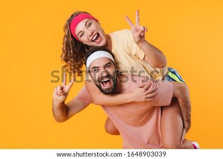 Portrait of athletic happy couple smiling while doing piggyback  Stock photo © deandrobot