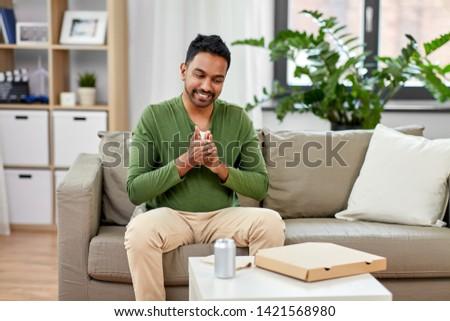 smiling indian man eating takeaway food at home Stock photo © dolgachov