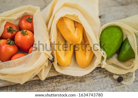 Fresh greens in a reusable bag on a stylish wooden kitchen surface. Zero waste concept Stock photo © galitskaya