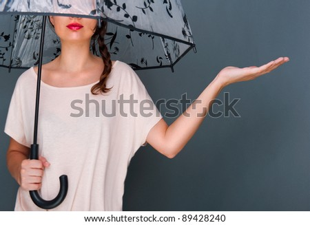 Young fashionable woman holding umbrella standing against grey b stock photo © HASLOO