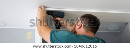 Stock photo: Man putting up a shelf
