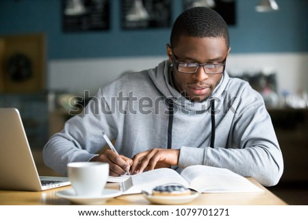 Young concentrated african man holding book in hands and reading Stock photo © deandrobot