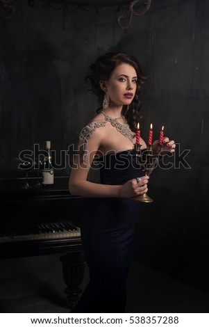 beautiful young woman in black dress next to a piano with candelabra candles and wine dark dramatic stock photo © andreonegin