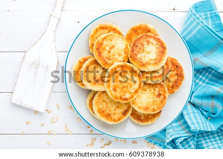 Cottage cheese pancakes with oats, syrniki on white rustic