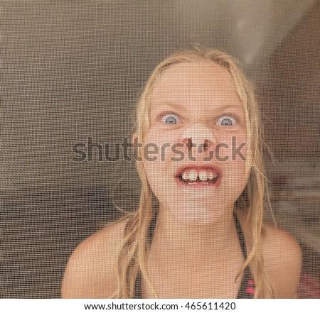 Girl pressing nose against screen door Stock photo © IS2