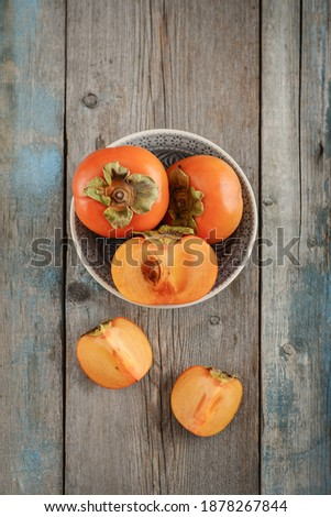 Stock photo: Autumn harvest Persimmon fruits in bowl on a wooden table backgr