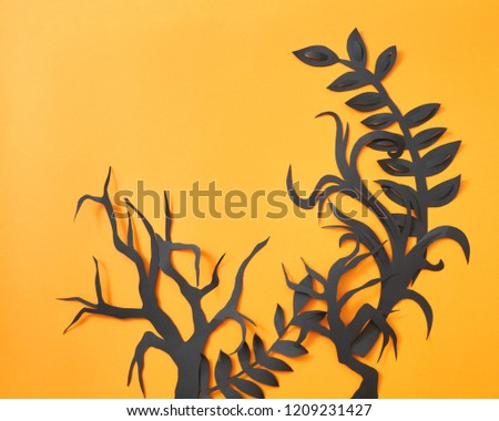 Mystical pattern of black paper handcraft leaves and trees on an orange background with space for te Stock photo © artjazz