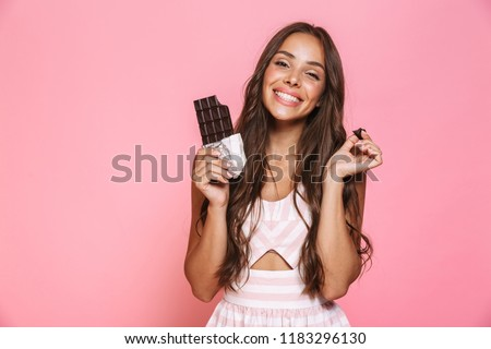 Photo of lovely woman 20s wearing dress smiling and eating choco Stock photo © deandrobot