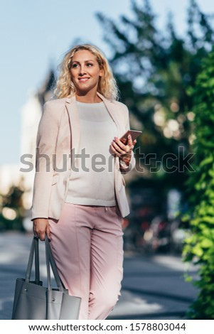beautiful smart casual woman wearing pink suit and holding brief Stock photo © feedough