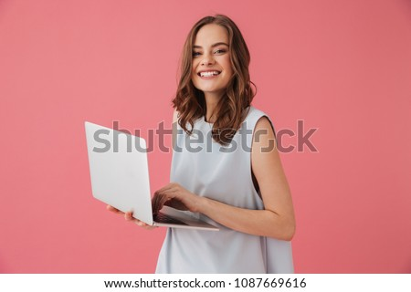 Beautiful woman isolated over pink background using laptop computer typing showing okay gesture. Stock photo © deandrobot