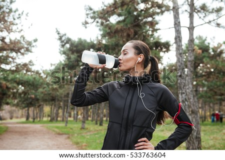Young sports lady in park outdoors listening music with earphones. Stock photo © deandrobot