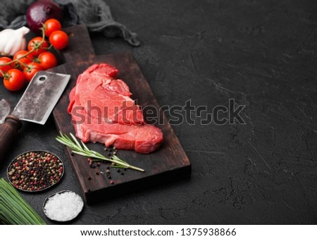 Fresh raw organic slice of braising steak fillet on black background. Stock photo © DenisMArt