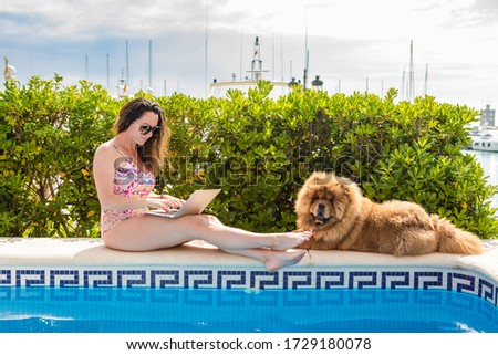 Young female freelancer sitting near the pool with her laptop in the hotel browsing in her smartphon Stock photo © galitskaya