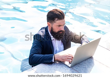 Foto stock: Young freelancer working on vacation next to the swimming pool