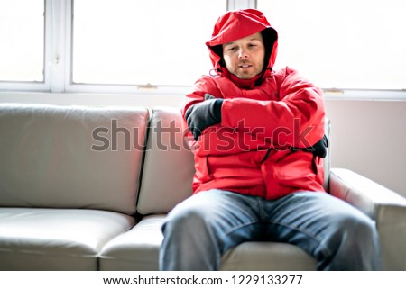 A Man With Warm Clothing Feeling The Cold Inside House on the sofa Photo stock © Lopolo