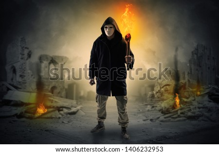 Stockfoto: Man coming with burning flambeau at a catastrophe scene concept