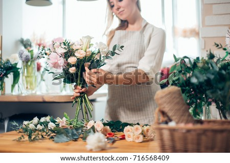 Young woman florist is making bouquet with fresh flowers roses living coral color at the table with  Stock photo © artjazz