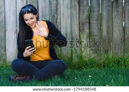 şaşırtıcı güzel bir kadın oturma çim konuşma cep telefonu Stok fotoğraf © deandrobot