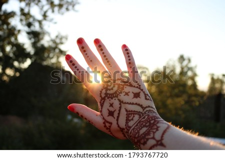 Young woman with a picture on the hand of henna - mehendi drinks coffee in the morning on the balcon Stock photo © galitskaya