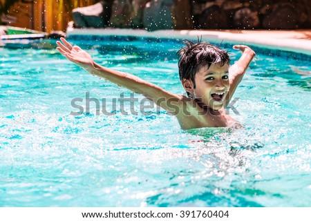 Young boy kid child splashing in swimming pool having fun leisure activity Stock photo © galitskaya