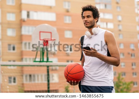 Young mixed-race athlete with ball and smartphone texting after game Stock photo © pressmaster