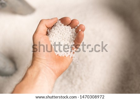 Hand of young male worker of large modern factory holding polymer granules Stock photo © pressmaster