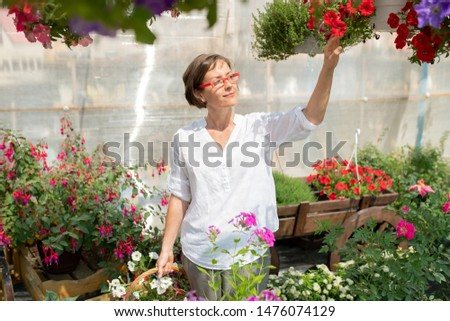 Happy young woman in casualwear touching one of potted petunias Stock photo © pressmaster