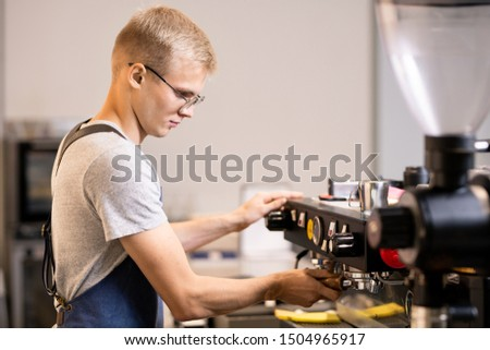 Young owner of small cozy cafe going to prepare coffee for his clients Stock photo © pressmaster
