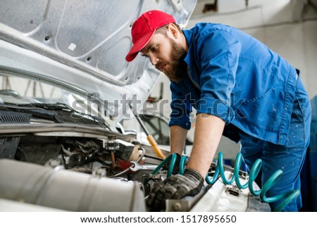 Young technician in workwear bending over engine of car or lorry Stock photo © pressmaster