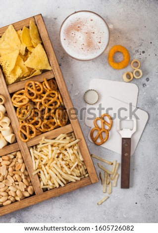 Glass of craft lager beer and opener with box of snacks on wooden background. Pretzel,salty potato s Stock photo © DenisMArt
