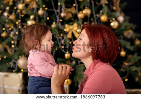 A christmas toddler with is mother in front of a fir. Stock photo © Lopolo