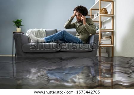 Man vergadering sofa roepen loodgieter vloer Stockfoto © AndreyPopov