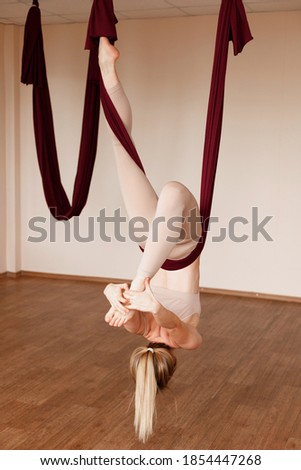 Woman in sportswear does exercises on the Aero yoga on the beach Stock photo © ElenaBatkova