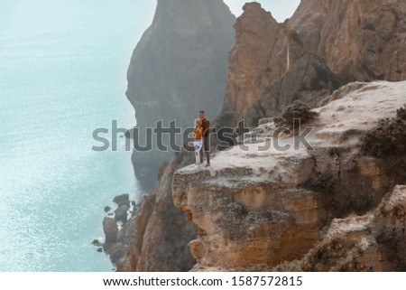 A young couple of sweethearts cuddle on top of a stone mountain with a backdrop of rocks Stock photo © ElenaBatkova