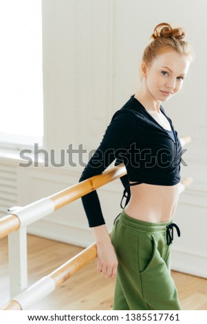 Sideways shot of attractive slim female dancer stands back to ballet barre, stretches body before tr Stock photo © vkstudio