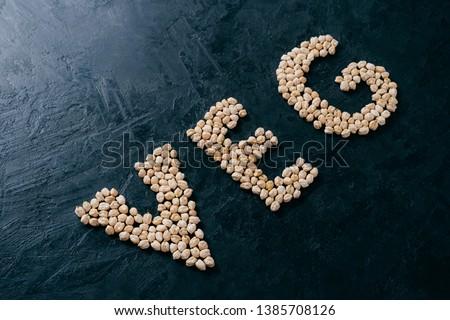 Natural food ingredient. Chickpea shaped in letter veg on dark background. Bio nut seeds. Organic ga Stock photo © vkstudio