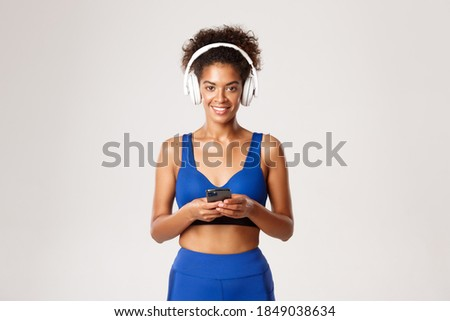 Attractive young healthy african sportswoman listening to music Stock photo © deandrobot