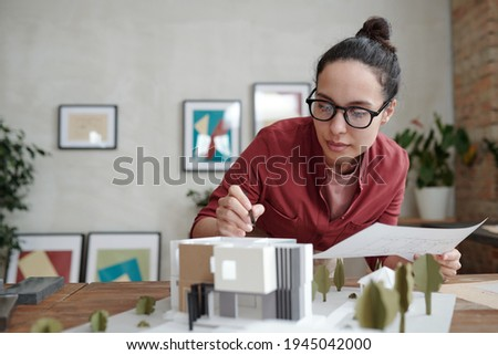 young architect bending over desk with blueprints and model Stock photo © photography33