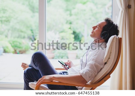 Man Listening To MP3 Player On Headphones Relaxing Sitting On So Stock photo © monkey_business