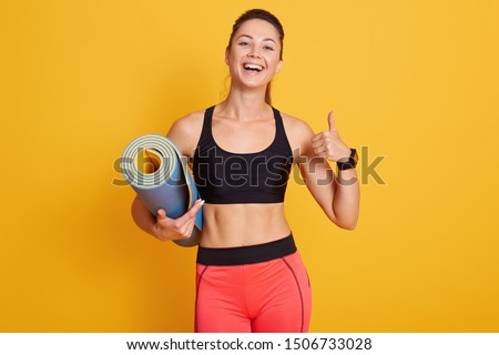 Young woman showing thumbs up sign with carrying exercise mat Stock photo © bmonteny