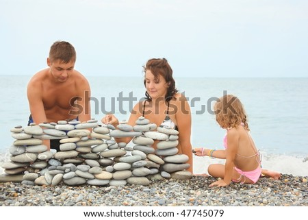Father, mother and little girl near construction of pebbles. sea in out of focus. Stock photo © Paha_L