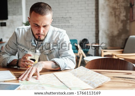 Young man drinking coffee while visiting the business district o Stock photo © Kzenon