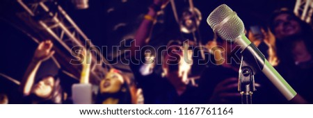 Close-up of microphone  against friends looking at mobile phone in nightclub Stock photo © wavebreak_media