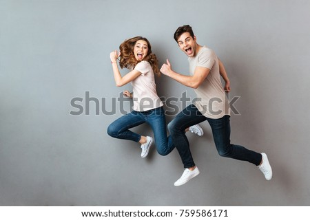 happy casual couple celebrating success with hands in the air stock photo © feedough